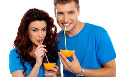 Couple cuddling and sipping orange juice Stock Photos