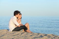 Couple cuddling sitting on the sand of the beach. Watching the sea royalty free stock photography