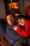 Couple Cuddling On Sofa By Cosy Log Fire. Middle Aged Couple Cuddling On Sofa By Cosy Log Fire Royalty Free Stock Photos
