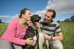Couple cuddling their dog. In green field Royalty Free Stock Photos