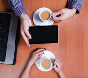 Couple  with a cup of coffee reading news Royalty Free Stock Image