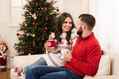 Couple with cups at christmastime. Happy young couple drinking tea and smiling each other at christmastime stock photos