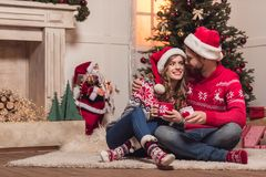 Couple with cups at christmastime. Happy young couple with cups embracing and smiling each other at christmastime stock image