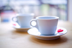 Couple cups with coffee decorated by red hearts on wooden table. Royalty Free Stock Images