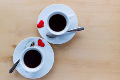 Couple cups with coffee decorated by red hearts on wooden table. Stock Image