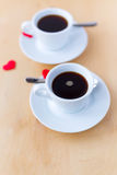 Couple cups with coffee decorated by red hearts on wooden table. Stock Photos