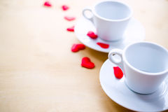 Couple cups decorated by red hearts on wooden table. Stock Photos