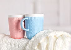 Couple of cups with knitting pattern, pink and blue color are on the warm white knitted blanket Stock Photos