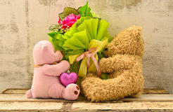 Couple of cute bear dolls holding roses bouquet Royalty Free Stock Photography