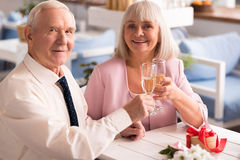 Couple of cute elderly people drinking champagne. It might get dizzy. Wonderful lovely senior people having champagne during their engagement celebration in a Royalty Free Stock Photo