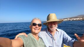 Couple of cute mature people or senior enjoying and having fun together in the middle of the sea or ocean with a small boat or din