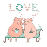 Couple of cute pigs sitting on a bench, the bird sings their song. Couple of cute pigs sitting on a bench. Boar boy holding acorns, piggy girl holding flowers Royalty Free Stock Image