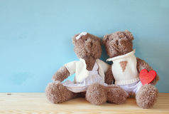 Couple of cute teddy bears holding hearts. Valentines day concept. Couple of cute teddy bears holding heart, sitting on wooden table Royalty Free Stock Images