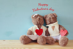 Couple of cute teddy bears holding hearts. Valentines day concept. Couple of cute teddy bears holding hearts, sitting on wooden table Stock Image