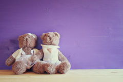 couple of cute teddy bears hugging on wooden table Stock Photo