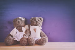 couple of cute teddy bears hugging on wooden table Royalty Free Stock Photo