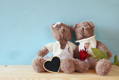 Couple of cute teddy bears sitting on wooden table Stock Images