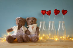 Couple of cute teddy bears sitting on wooden table Stock Image
