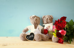 Couple of cute teddy bears sitting on wooden table Royalty Free Stock Photo