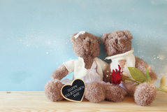 Couple of cute teddy bears sitting on wooden table Stock Photography