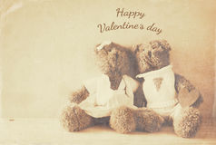 Couple of cute teddy bears sitting on wooden table. Valentines day concept. Couple of cute teddy bears sitting on wooden table. Sepia style filtered with texture Stock Image