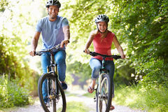 Couple On Cycle Ride In Countryside. Wearing Helmets Smiling Royalty Free Stock Images