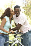 Couple On Cycle Ride in Park. African American Couple On Cycle Ride in Park Smiling royalty free stock photography