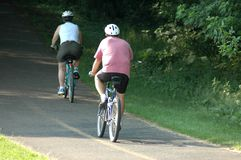 Couple cycling. Along path Stock Image