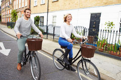Couple Cycling Along Urban Street Together Stock Image