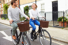 Couple Cycling Along Urban Street Together Royalty Free Stock Images