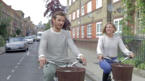 Couple Cycling Along Urban Street Together Royalty Free Stock Photo