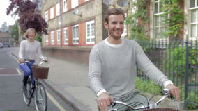 Couple Cycling Along Urban Street Together stock footage