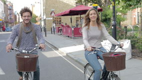 Couple Cycling Along Urban Street Together Stock Photo