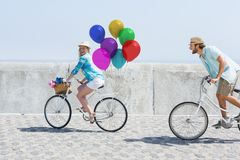 Couple cycling with balloons in sunshine Royalty Free Stock Images