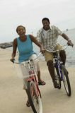 Couple Cycling On Beach Stock Images