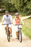Couple Cycling In Countryside Wearing Safety Helme Stock Photo