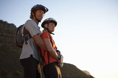 Couple in cycling helmets standing on mountain, looking at view, man embracing woman, side view Royalty Free Stock Photos
