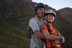 Couple in cycling helmets standing in mountain valley, smiling, side view, portrait Stock Photography