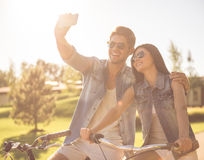 Couple cycling in park. Beautiful stylish couple is making selfie using a smartphone and smiling while cycling in the park Royalty Free Stock Photos