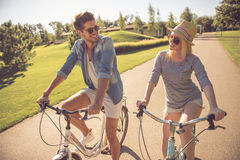 Couple cycling in park. Beautiful couple is talking and smiling while cycling in the park Stock Images