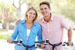 Couple Cycling On Suburban Street royalty free stock photo