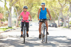 Couple Cycling On Suburban Street Royalty Free Stock Images