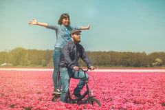 Couple cycling through tulip field Stock Images