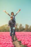 Couple cycling through tulip field Royalty Free Stock Photos