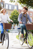 Couple Cycling Through Urban Park Together Stock Photo