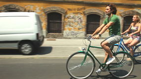 Couple cycling. Young couple enjoying cycling through city in summer stock footage