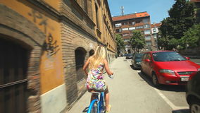 Couple cycling. Young woman cycling in city street meeting up with her boyfriend on bike stock footage