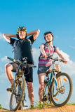 Couple of cyclists in helmets on bikes. A couple of cyclists in helmets on bikes posing Royalty Free Stock Photography