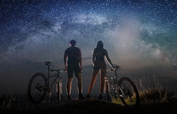 Couple cyclists with mountain bikes at night under starry sky stock image
