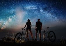 Couple cyclists with mountain bikes at night under starry sky. Silhouette of men and women bikers enjoying night sky with stars and Milky way. Bikers with Royalty Free Stock Photo